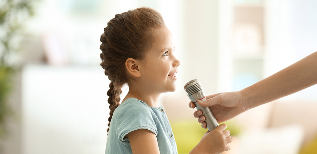 Female hand giving microphone to cute little girl at home